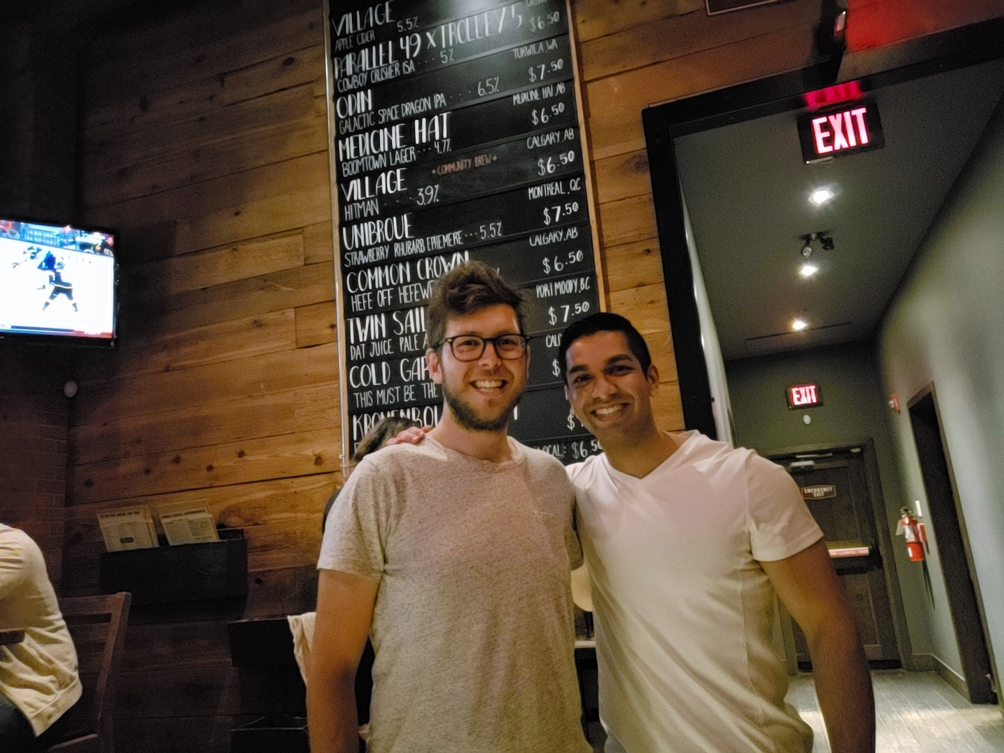 Ben and Umair are standing in front of a beer list.