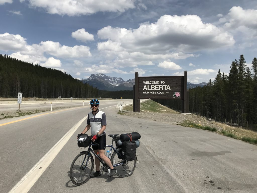 A man standing on a bicycle with camping gear strapped to the back, background features the Welcome to Alberta sign and the rocky mountains