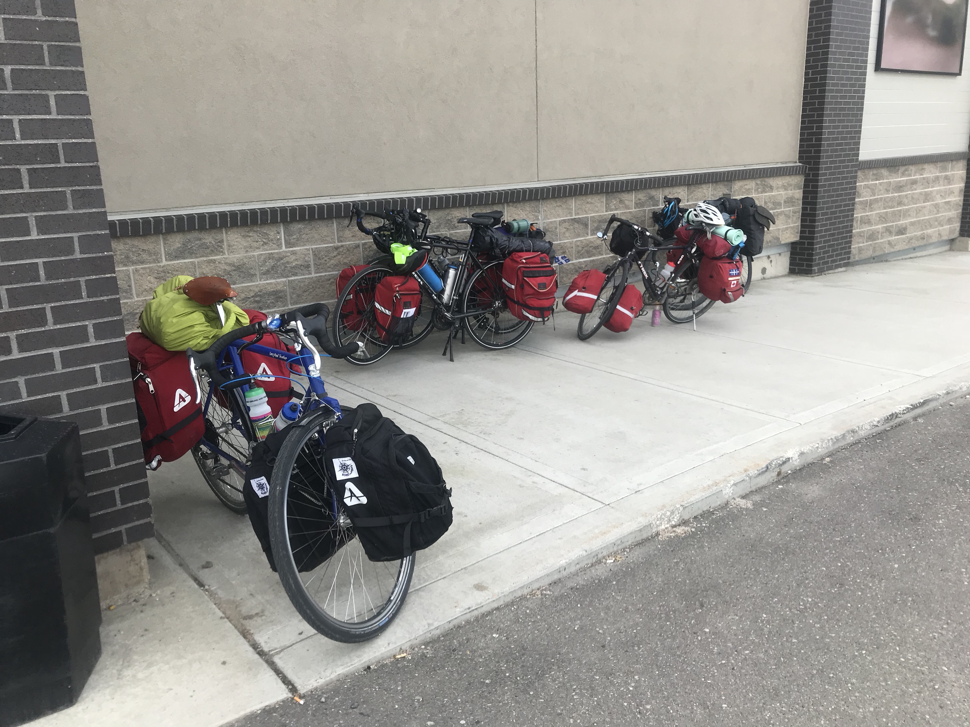 Five bikes loaded with gear leaning against a wall