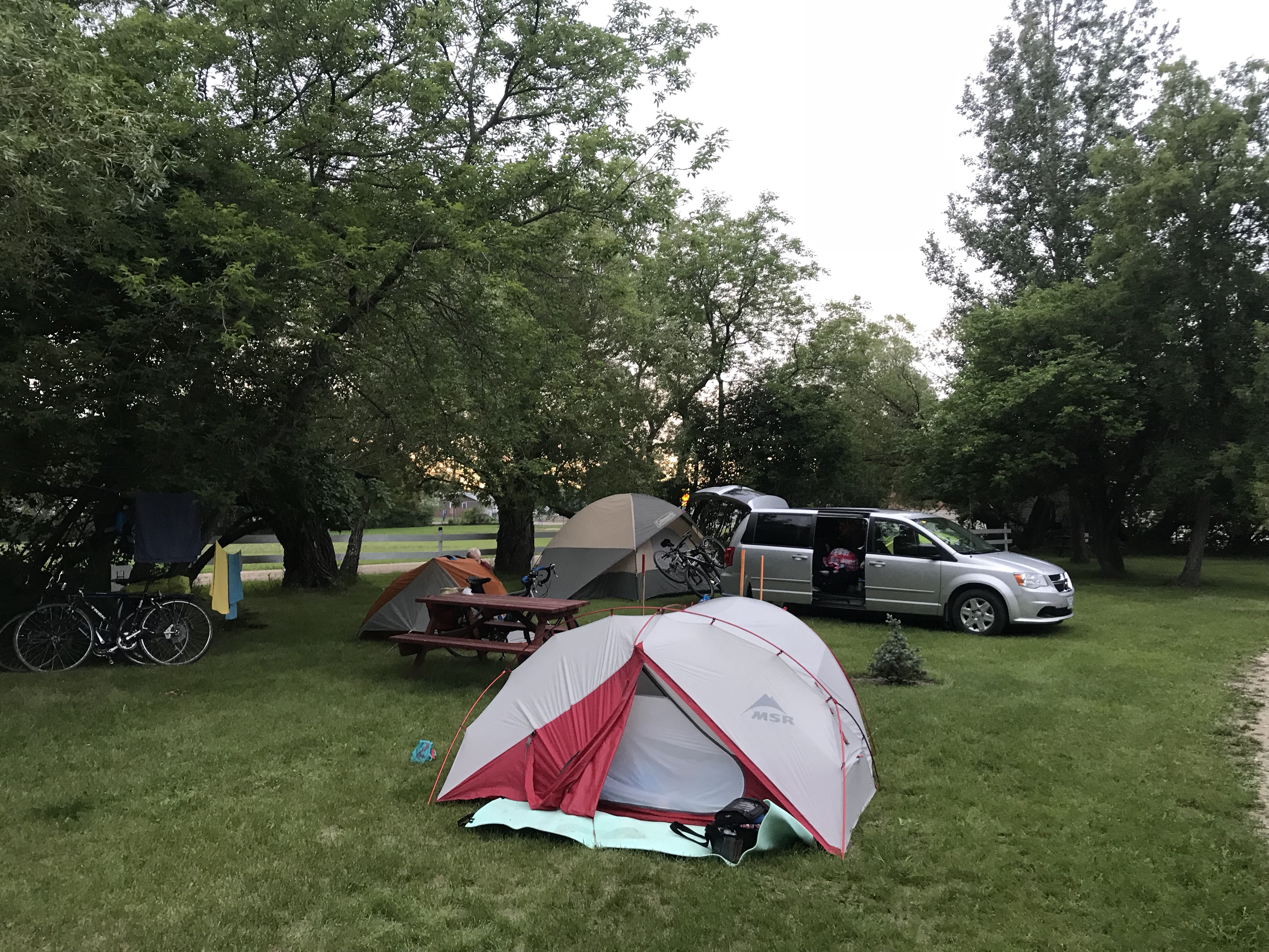 A backpacking tent in the foreground and a large van with bikes on the back and a giant tent beside it in the background