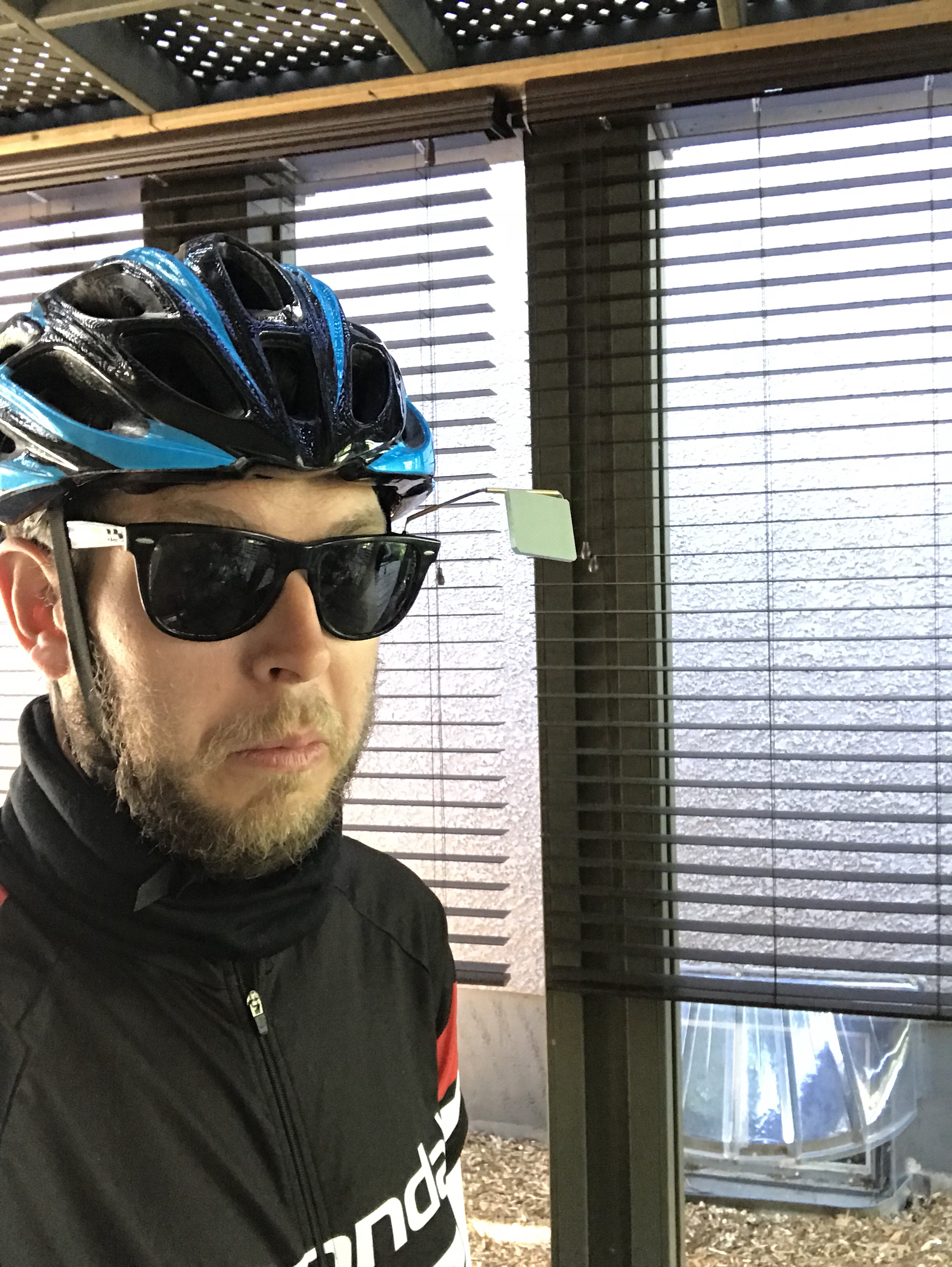 Ben pictured in cycling clothing, a helmet, glasses, and a mirror protruding from the glasses