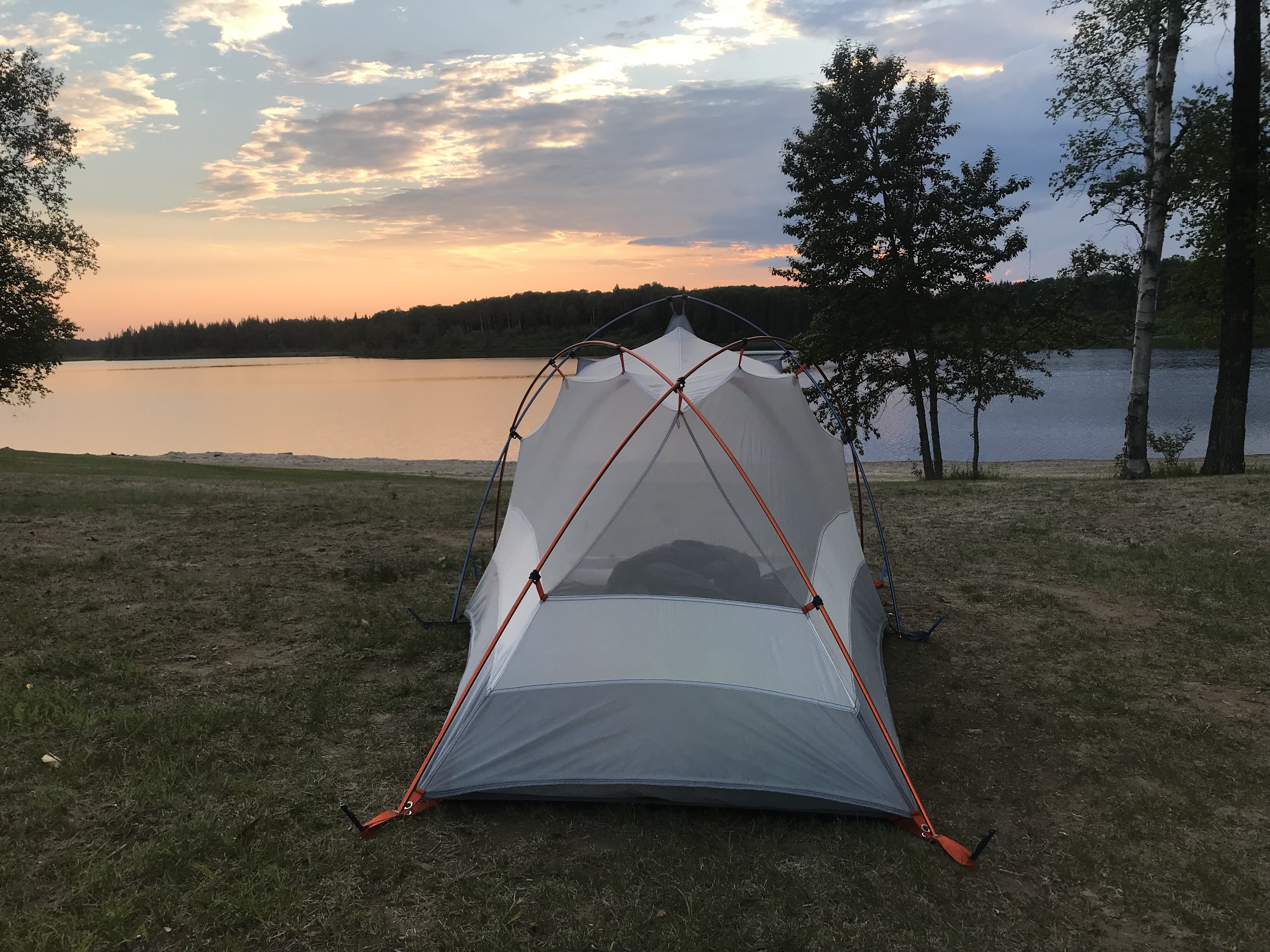Setting sun over a lake, red cloudy sky, and tent in foreground
